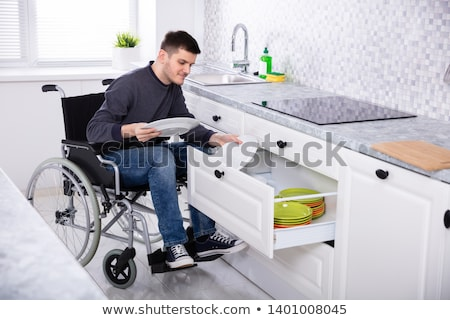Disabled Man Sitting On Wheelchair Arranging Plates Stock photo © AndreyPopov