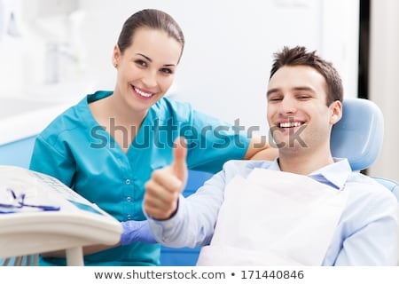 Glimlachend patiënt tonen tandheelkundige kliniek Stockfoto © dolgachov