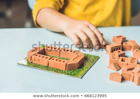 Close up of child's hands playing with real small clay bricks at the table. Toddler having fun and b stock photo © galitskaya