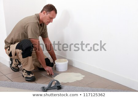 Carpet fitter applying adhesive over an old tiled floor Stock photo © photography33