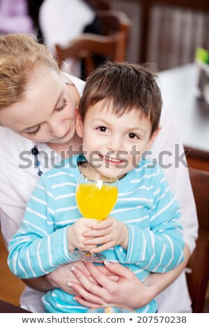 Child drinking juice in his mother's lap Stock photo © photography33