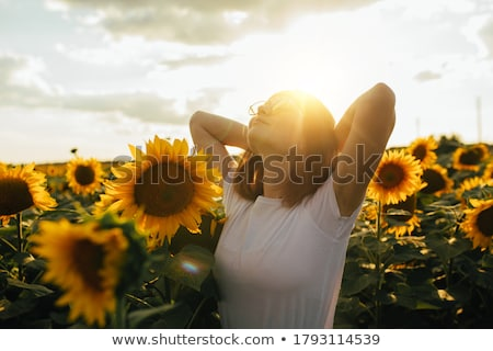 attractive young girl with a sunflower stock photo © nejron