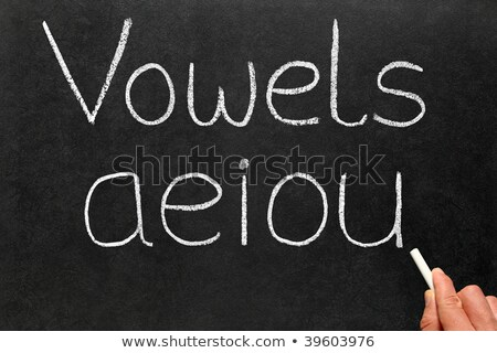 A teacher writing the five vowels letters on a blackboard. Stock photo © latent