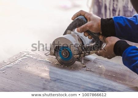 Worker man cuts the ceramic tile  Stock photo © OleksandrO