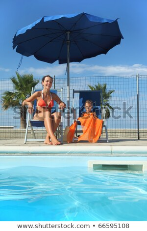 Smiling woman in swimsuit sitting near fence Stock photo © dash