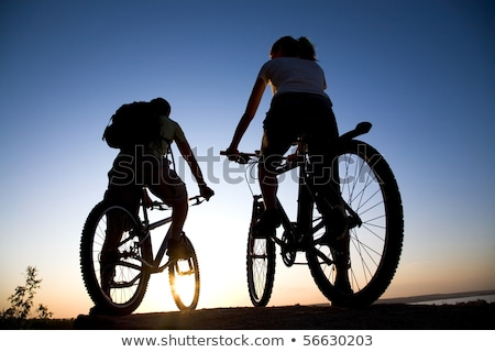 cyclist resting with mountain bike on the rock at sunset stock photo © maxpro
