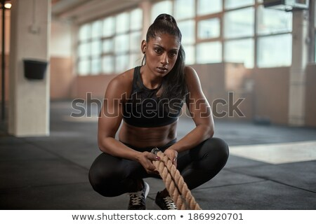 Serious strong sports lady sitting in gym Stock photo © deandrobot