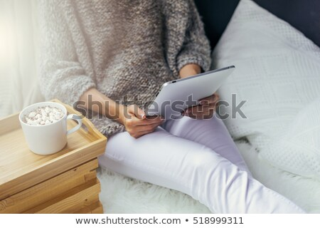 close up of woman with cocoa cup and cookie in bed stock photo © dolgachov