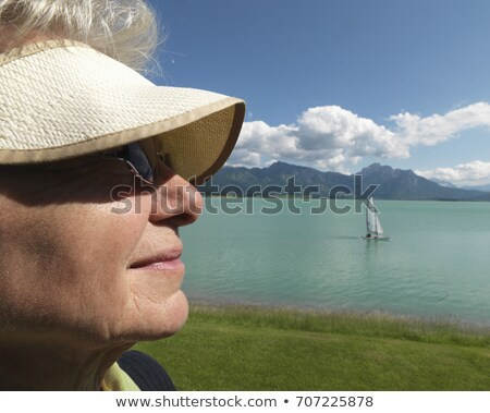 Senior woman gazing across lake Stock photo © IS2