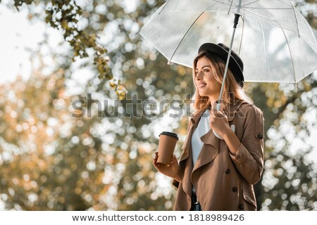 smiling woman holding umbrella stock photo © is2
