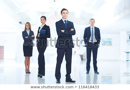 portrait of confident handsome elegant responsible businessman looking at watches on black backgroun stock photo © traimak