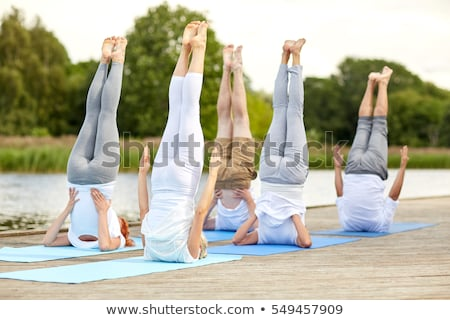 woman making yoga in shoulderstand pose outdoors stock photo © dolgachov
