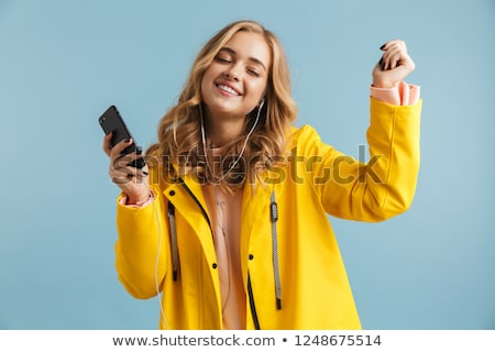 Image of beautiful woman 20s wearing yellow raincoat holding mob Stock photo © deandrobot