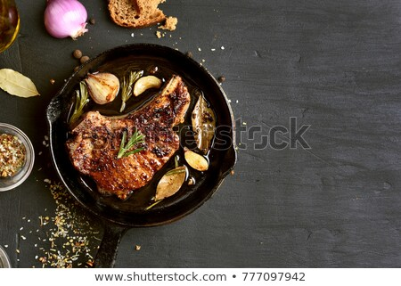 Baked roast pork meat in black frying pan Stock photo © artsvitlyna
