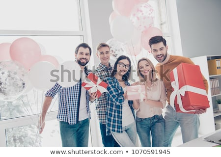 Cheerful young woman with birthday gifts standing by table Stock photo © pressmaster