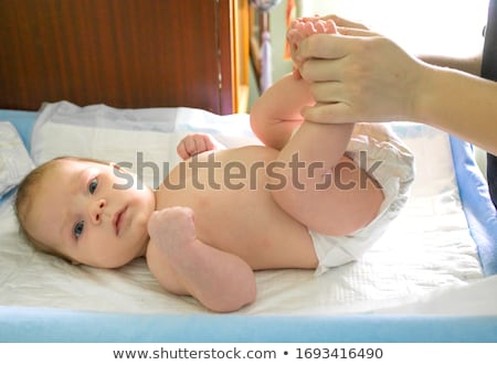 Beautiful little baby boy lying on a white sheet on the bed Stock photo © ElenaBatkova