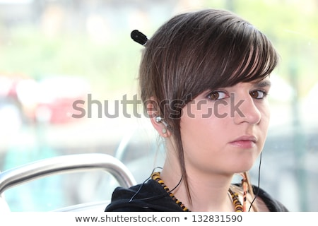 Closeup of girl with earphones sitting on a tram Stock photo © photography33