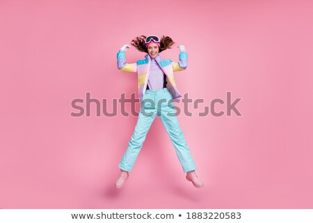 Skiing. Beautiful young happy girl flies on skis Stock photo © orensila