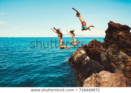 Barátok ugrik tenger boldog naplemente víz Stock fotó © lubavnel