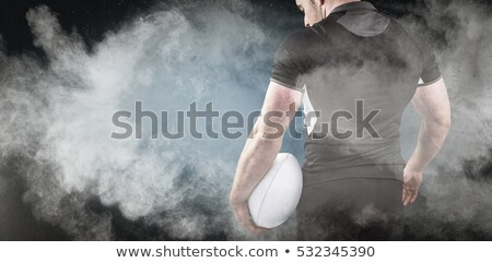 Stock photo: Composite image of tough rugby player holding ball