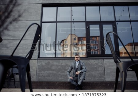 serious young business man in checkered suit sitting  Stock photo © feedough