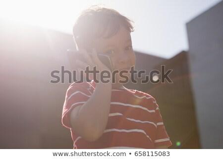 Ver menino falante telefone móvel em pé Foto stock © wavebreak_media