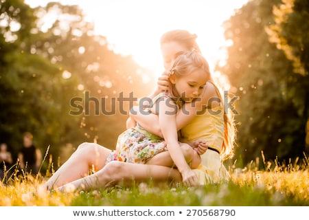 Szülők ölelkezés lánygyermek fű fiatal mozog Stock fotó © LightFieldStudios