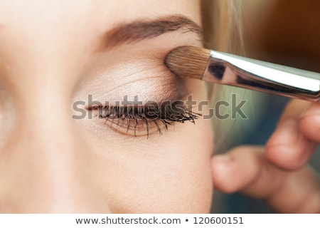 Beautiful model applying eyeliner close-up on eye. Make-up Stock photo © serdechny