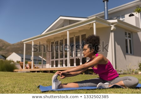 Front view of beautiful young fit mixed-race woman performing a yoga pose on a blue mat in the backy Stock photo © wavebreak_media