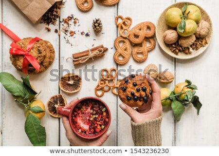 Hands of girl holding appetizing cupcake with blackcurrant and hot herbal drink Stock photo © pressmaster