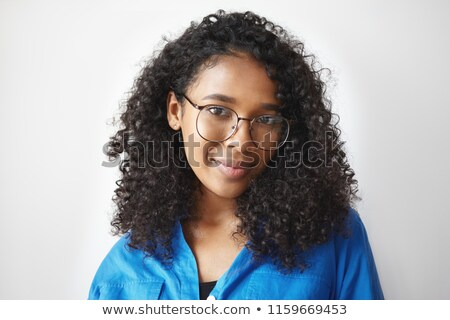 Headshot of beautiful smiling dark skinned woman wears optical glasses, holds modern cell phone, has Stock photo © vkstudio