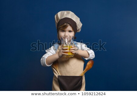 Little girl wearing hat drinking glass of orange juice Stock photo © photography33