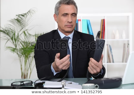 Businessman trying to decide which phone to use Stock photo © photography33