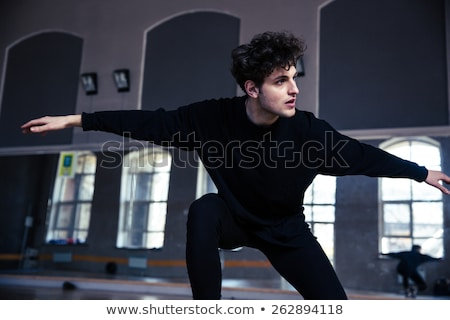 Stock photo: Young male dancer stretching at gym