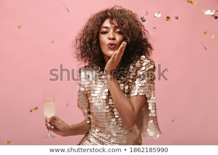 smiling attrative young woman standing and drinking champagne stock photo © deandrobot