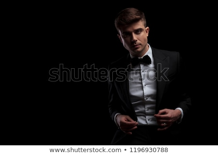 stylish young man sits and buttons his black suit Stock photo © feedough