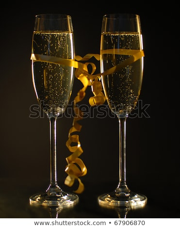 sparkling glasses of champagne with gold serpentine on black background bokeh effect with sign happ stock photo © marysan