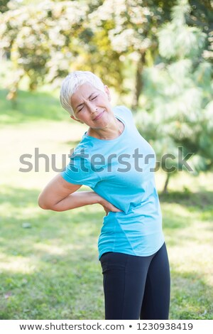 sporty senior woman having a back pain stock photo © boggy