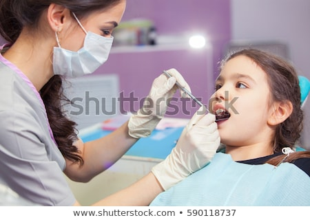 dentist treating kid teeth at dental clinic Stock photo © dolgachov