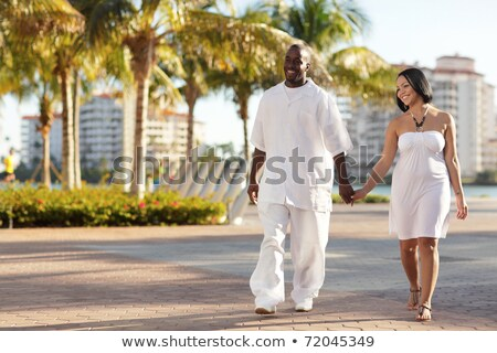 Image of african american couple in colorful clothes holding pal Stock photo © deandrobot
