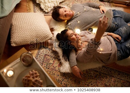 happy couple with garland lying on floor at home Stock photo © dolgachov