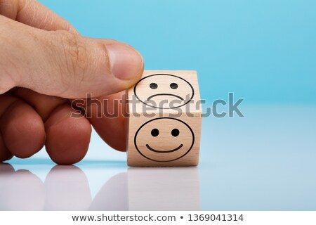 sad and happy face wooden block holding by persons hand stock photo © andreypopov