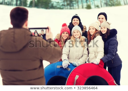 friends with snow tubes taking photo by tablet pc Stock photo © dolgachov