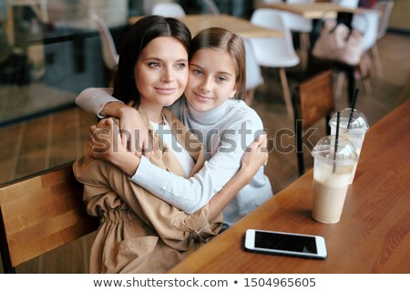 Serene young woman and her daughter sitting in embrace while relaxing in cafe Stock photo © pressmaster