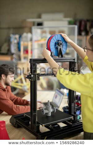 Young woman putting new spool with filament on 3d printer before starting work Stock photo © pressmaster