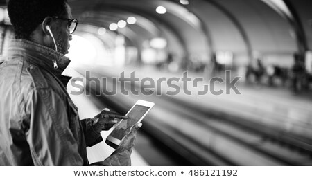 Contemporary business traveler with mobile phone standing by reception counter Stock photo © pressmaster