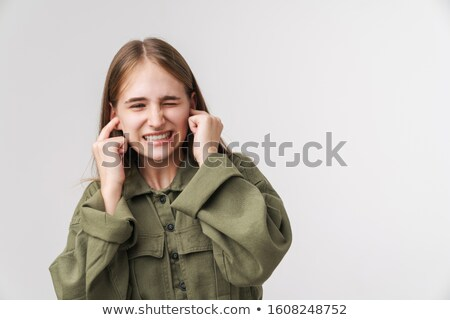 Photo of irritated young woman plugging her ears and looking aside Stock photo © deandrobot