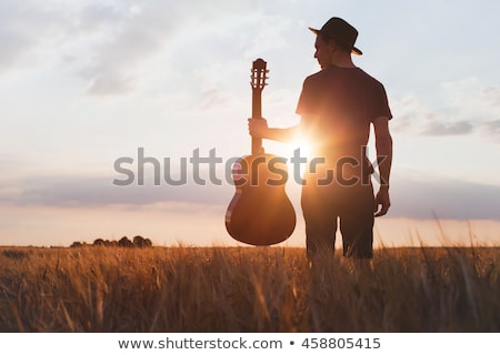 A handsome, mature musician posing with his guitar.