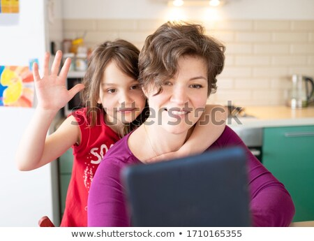 young girl talking to her freind through cellphone stock photo © stockyimages