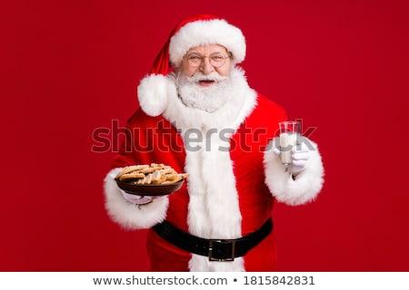 santa claus eating cookies with milk stock photo © hasloo